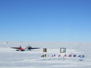 Ceremonial South Pole, surrounded by the flags of the Antarctic Treaty nations, with a tourist plane in the background.