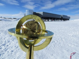 South Pole Marker, with the South Pole Station in the background.