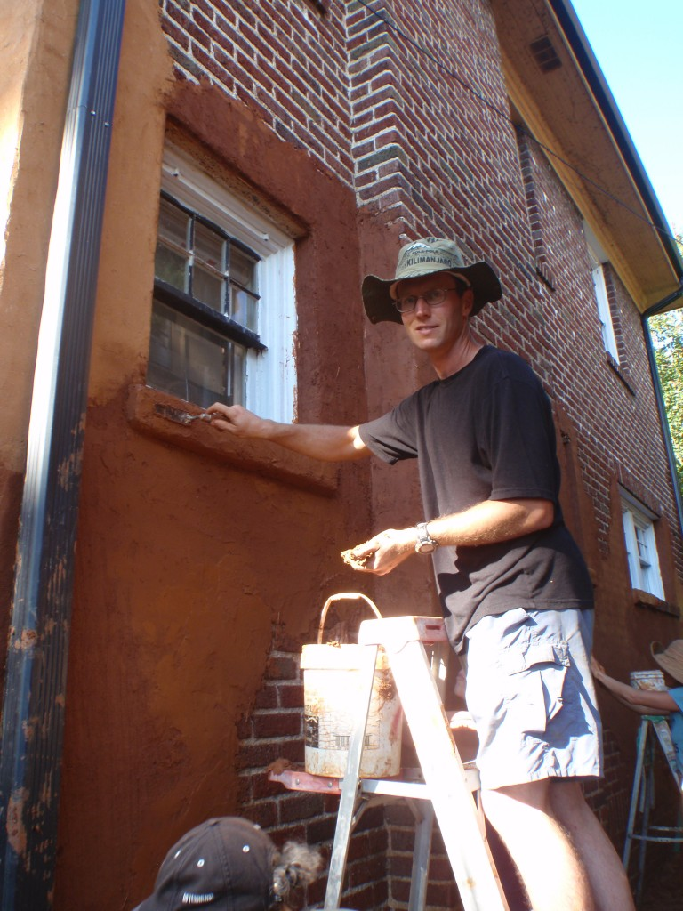 Applying and earthen plaster to a wall.