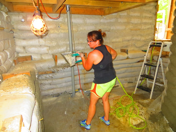 Denise sprays papercrete with a mortar sprayer onto the walls of the lower level of the cistern room.