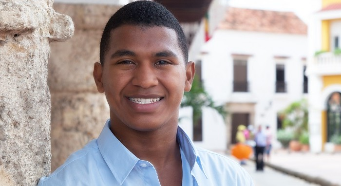 Young guy in a blue shirt in a colonial town with historic buildings in the background